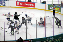 Several hockey players in either white and blue or black and grey uniforms watch as one player shoots the puck into his opponent's net