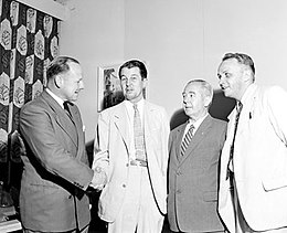 Four men in civilian clothes, two of whom are shaking hands