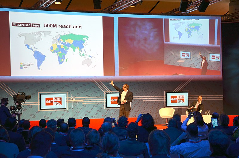 Archivo:2014-03-14 CeBIT Global Conferences, Jimmy Wales, Founder Wikipedia, (26) On stage showing the world for Wikipedia Zero (500 millions), while Brent Goff is still listening.jpg