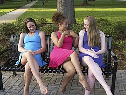 3 barefoot females smiling and sitting on a bench.jpg