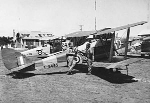 Two airmen assigned to No. 7 Elementary Flying School with two of the unit's Tiger Moth aircraft at Western Junction Aerodrome