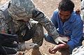 A GI gives first aid in Iraq.jpg