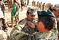 A U.S. Army paratrooper pins Army Airborne wings onto a Jordanian soldier's uniform after a friendship jump June 12, 2013, in Zarqa, Jordan, during exercise Eager Lion 2013 130612-A-ZM282-333.jpg