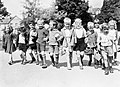 A group of smiling evacuees from Rotherhithe in Kent with gas mask boxes hold hands on a walk in Reading during 1940. D824.jpg