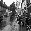 A union flag hangs in the main street of Les Andelys in Normandy as British forces arrive, 31 August 1944. The woman in the foreground is Madame Scarlett, wife of an expatriate Englishman and owner of the Hotel B9869.jpg