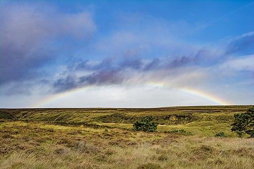 A vibrant full rainbow over Ogden Water (Unsplash)
