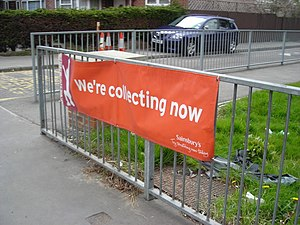 Sainsbury's Active Kids - A Sainsbury's Active Kids banner outside a school. Tokens are collected at stores, and are redeemed for sports equipment.