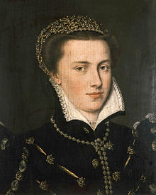 A serene brown-haired woman, probably in her twenties, with a round face and clear skin and eyes, wears a richly embroidered and jeweled gown, wearing a jeweled headpiece. She wears gems in her ear lobes, and has a gem necklace. Her face is framed by a white collar with intricate embroidery work on its edging. Her demeanor is composed, and she has a slight smile.