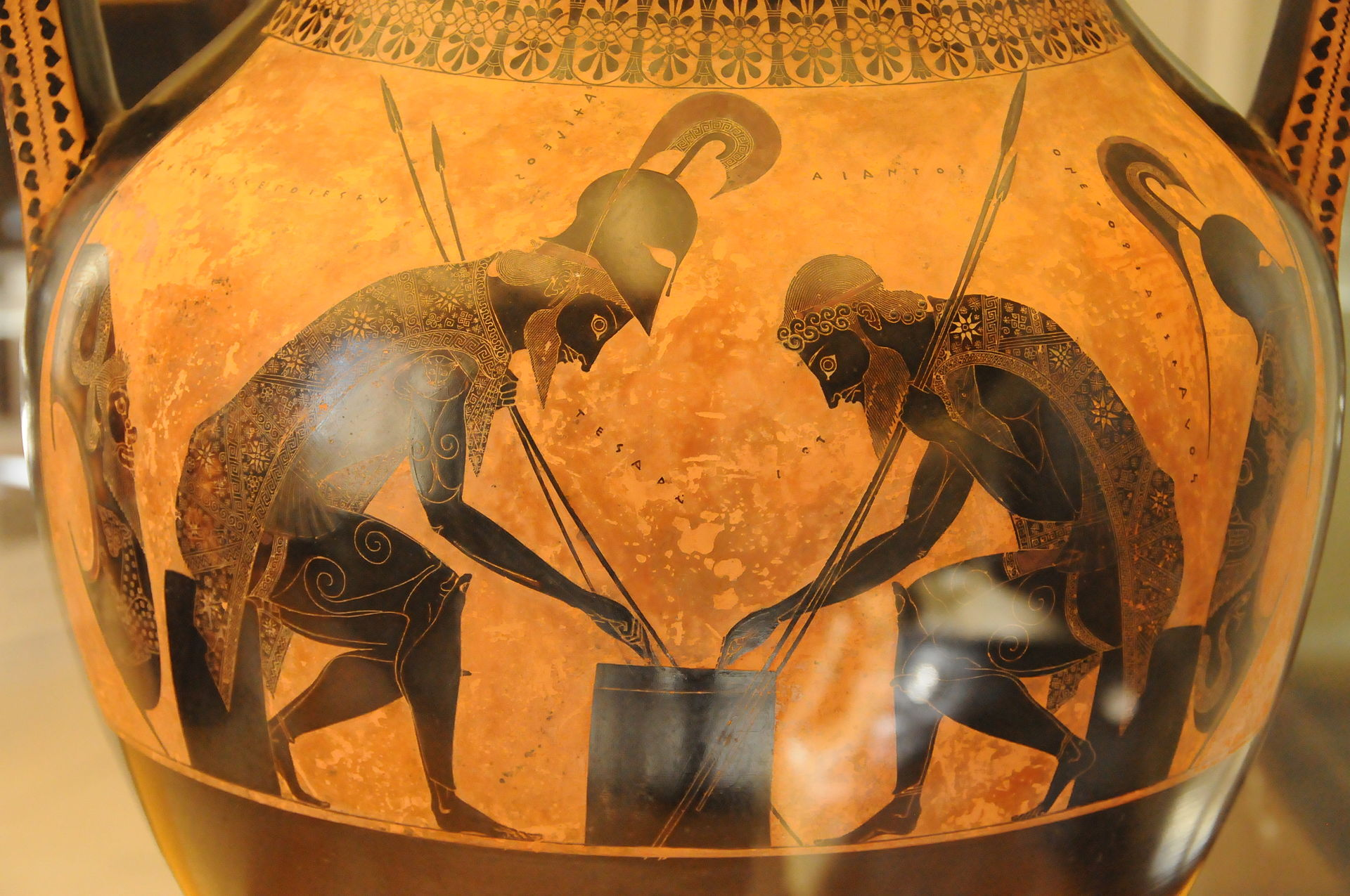 Achilles and Ajax play a board game. They are distinguished from one another by their captions.