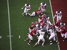 American football players in middle of a running play near the endzone.