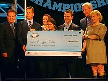 A high school student stands behind a large blue check. Behind her stand six adults in suits. The check has a National Vocabulary Championship logo in the top left and is written out to Aliya Deri for the amount of $40,000. The check is dated March 10, 2008.