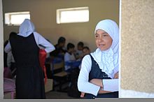 An Iraqi girl, right, observes the festivities during the opening ceremony of the newly-renovated al Duwaya Primary School in northern Baghdad, Iraq, March 20, 2011 110320-A-IN286-711.jpg