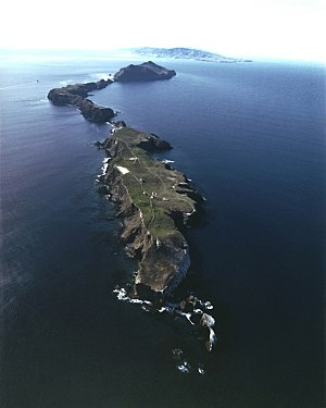 Anacapa Island - Aerial view of Anacapa with the lighthouse and coastguard station on East Anacapa in the foreground and Middle and West Anacapa behind. Santa Cruz Island is on the horizon.