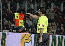 Photo d'un arbitre de touche en jaune levant son drapeau avec les tribunes en fond.