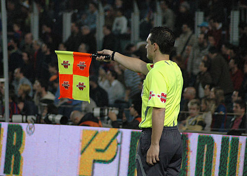 A Linesman signals that the offside offence was in the middle of the pitch; on the far side the flag would be pointed up at 45 degrees, for near the linesman it would be pointed down. Assistant referee 15abr2007.jpg