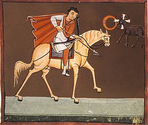 "Four Horsemen of the Apocalypse - The first Horseman, Conquest on the White Horse as depicted in the Bamberg Apocalypse (1000-1020). The first ""living creature"" (with halo) is seen in the upper right."