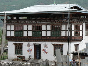 Architecture of Bhutan - A Bhutanese house in Paro with multi-colored wood frontages, small arched windows, and a sloping roof