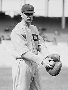 A black-and-white image of a man wearing a white old-style baseball uniform and holding a baseball with his right hand in the catcher's mitt on his left hand