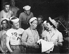 A military scene.  A woman dressed as a nurse holds a skirt she has just received from an enlisted man; she is pleased while he appears self-deprecating. Other enlisted men, many bare-chested, watch.