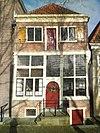 foto van Huis met van top beroofde gevel op houten pui boven stenen borstwering; in deurkalf gedateerd 1624. Inwendig houtskelet, spiltrap en insteek in voorhuis; galerij in achterhuis, balklaag op houten en stenen consoles. Achtertop hersteld