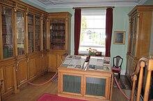 Foto av et laboratorium med glasskapslede trebokhyller på to vegger og et vindu på den tredje.  Det er et utstillingsvindu midt i rommet.