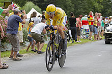 Bradley Wiggins riding a time trial bicycle wearing yellow cycling clothing