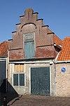Huis met trapgevel met bakstenen waterlijsten, rode banden en hoekversieringen in ijsselsteen