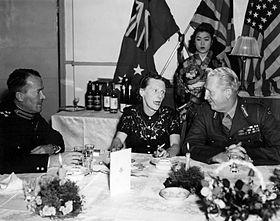 Two uniformed men talking to a woman at a dinner table