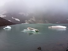 Small icebergs float in a small lake with volcanic rock in the background