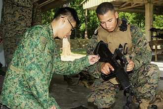 Singapore Guards - Singapore Guardsmen and US Marines examine a SAR-21 prior to a joint small-arms live-fire exercise during CARAT 2009.