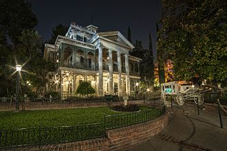 Haunted Mansion - Attraction exterior in the evening.