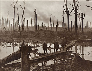 A group of soldiers walk across wooden duckboards that have been constructed over a waterlogged and muddy field. Shattered trees dot the landscape, with a low lying haze in the background