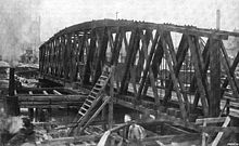 Black and white photograph showing a wooden railroad bridge