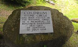 "A circular boulder takes up most of the image; behind it can be seen green grass. On the boulder is a light-grey plaque. On this plaque are written the words: ""Coldrum Stone Circle has been vested in The National Trust as a Memorial to Benjamin Harrison 1837–1921 of Ightham 10 July 1926"". All of the letters are in capital letters; those stating ""Coldrum Stone Circle"" are larger than the others."