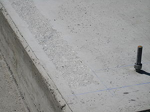 Scabbling - Closeup of scabbled concrete during the process of preparing a foundation for grouting under a new equipment skid.