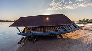 Contre-jour photograph of the careening of a pirogue at sunset with sunlight through a hole in its roof Si Phan Don Laos.jpg