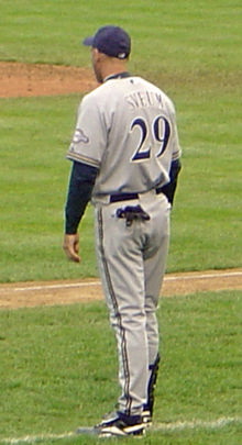 A man wearing a gray baseball uniform and navy-blue baseball cap facing away from the camera