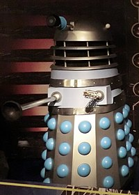 An original Dalek, coloured mostly silver and grey, with blue balls protruding from the skirt.