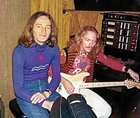 Two musicians sit side by side in a recording studio. Both men have long red hair. The man on the left wears a blue jumper and sits in a relaxed manner. The one on the right is tuning his guitar.
