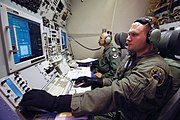 Inside military aircraft. Two personnel wearing green clothes and blue gloves manning communications consoles with wide displays.