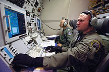 Inside military aircraft. Two personnel manning communications consoles with wide displays.
