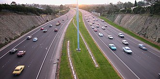 Eastern Freeway (Melbourne) - Eastern Freeway viewed facing the city at sunset from the Belford Road overpass, in Kew. The wide median, designed to accommodate a double-track railway, can be seen.