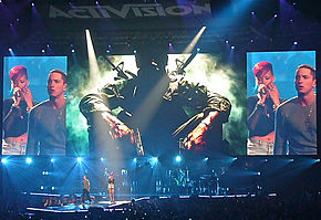 A large screen with the silhouette of a man, seated with two pistols, is in the center. Surrounding it are screens showing Eminem, who is to the right of Rihanna, the latter is holding a microphone and has short red hair.
