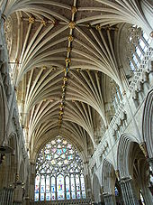 The interior of the nave at Exeter shows a great richness and diversity of decoration. Above the Gothic arcade runs an ornately sculptured blind gallery, above which rise clerestory windows full of Geometri tracery. The wide western window of nine lights beneath an upper rose fills the western end. The vault has many ribs of strong profile which spring out in clusters like palm branches.