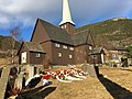 Fåvang Church (kirke) c. 1630, at Tromsnesvegen, Fåvang, Ringebu, Gudbrandsdalen, Oppland, Norway. Graveyard (kirkegård), cemetery wreaths, funeral flowers, springtime, Korstadkampen, etc. 2017-04-05 4074.jpg