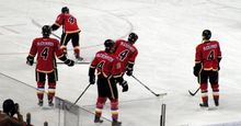 "View from behind of five hockey players, each wearing red uniforms with black trim. The back of all five players reads ""MCCRIMMON 4""."
