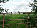 Gate, field, pylons, houses - geograph.org.uk - 1861701.jpg