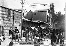 Soldiers on horseback trot along a road past several buildings watched by a group of civilians