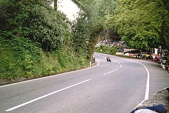 Glen Helen, Isle of Man - Racing motorcycle negotiating the entrance to Glen Helen turn, exiting uphill, set deep in the countryside with the entrance to the actual Glen and car park (shared with the closed restaurant) to the right, with many spectators around the outside of the bend