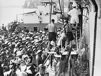 Operation Passage to Freedom - Refugees transfer from a French LCT landing craft to British carrier HMS Warrior at the port of Haiphong during the operation 4 September 1954